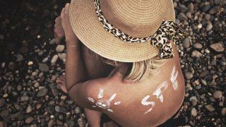 背中にSPFと日焼け止めで書かれた女性